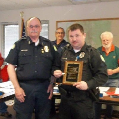 Police Chief and Select Board present Officer Stephane Goulet with life-saver commendation.